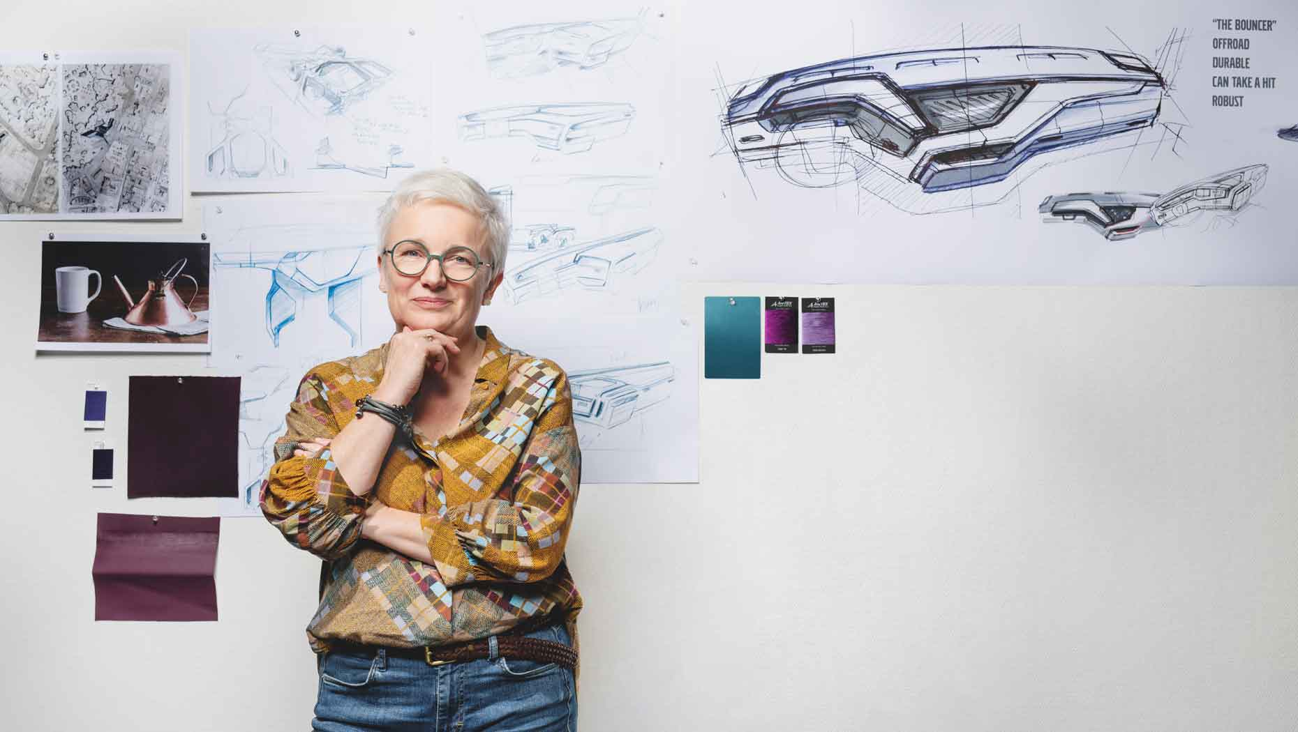 Carina Byström, Chief Designer Interior at Volvo Trucks stands in front of Volvo FM design sketches and colour samples on a wall